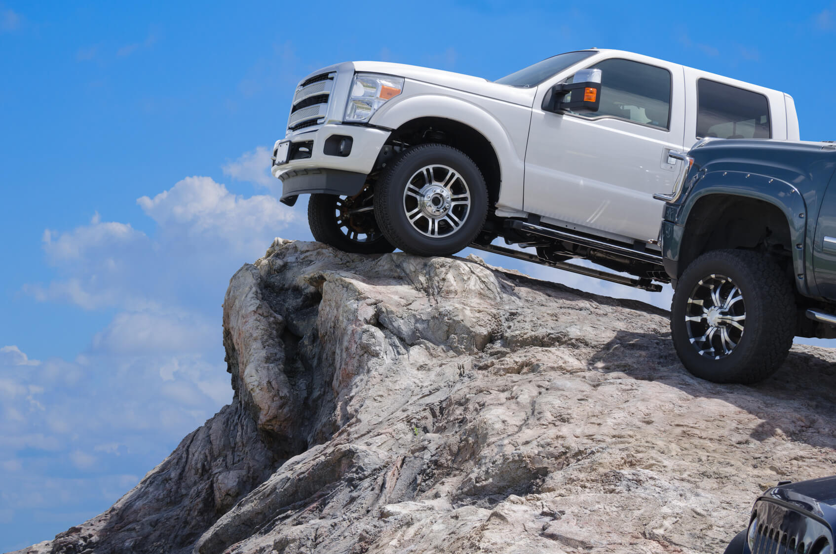 Big rugged trucks on the edge of a rocky cliff ledge